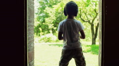 Boy standing in the doors with the view on garden and listening music, steadycam Stock Footage