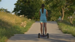 Woman on electric scooter climbs up the road Stock Footage