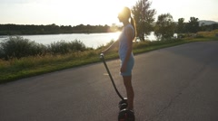 Woman on Segway rides to the sunset Stock Footage