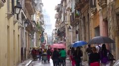 Crowds of people walk on the streets of Old Havana Cuba in the rain. Stock Footage