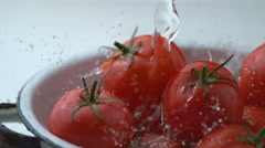 Water splashing onto tomatoes in slow motion, shot at 1000 frames per second on Stock Footage