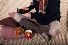 Young woman sitting on the floor and use the tablet. Cozy home atmosphere. Feet Stock Photos