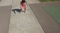 Young girl playing Hopscotch at park Stock Footage