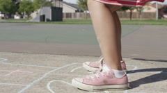 Young girl playing Hopscotch at park, closeup of feet Stock Footage