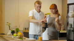 Happy couple making healthy organic juice in kitchen Stock Footage
