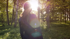 Girl in blue coat looking around and walking in the forest Stock Footage