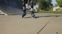 Boy Rollerblading at park, closeup of feet Stock Footage