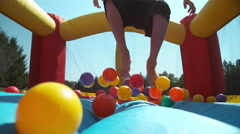Boy bouncing in inflatable play house, super slow motion Stock Footage