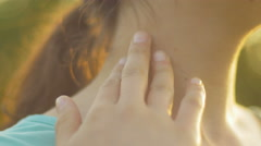 Close-up of female hands touching a neck in the sunlight Stock Footage