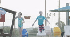 Slow motion shot of two kids jumping with balls to a pool Stock Footage