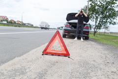 Car with a breakdown alongside the road, man sets the warning triangle Stock Photos
