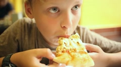 Close up shoot of cute boy sitting at table in fast food restaurant. Stock Footage