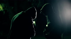 Two hooded criminals in dark park selling buying drugs Stock Footage