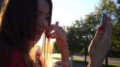 Beautiful brunette girl making selfie in the park, warm sunset colors. Slow Stock Footage