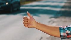 Young boy hitchhiking at road in summer day. Thumb up. Transportation. Cars Stock Footage