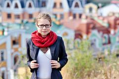 Young woman in glasses and a red scarf on back Stock Photos