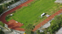 Helicopter Aerial view of Californian ball game and running athletic track Stock Footage