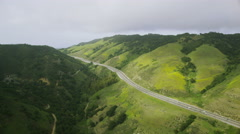 Aerial view of Californian hills road. Highway cuts through green land. Stock Footage