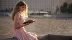 Beautiful girl on the waterfront with a book in their hands Stock Footage