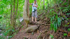 Tourist Hiking down an Embankment with her Baby, with Sound Stock Footage