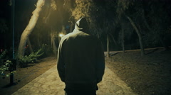 Suspicious hooded figure walks in a dark park at night,gimbal tracking Stock Footage