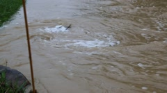 Rapidly Twirling Flood Waters form Eddy next to road surface Stock Footage