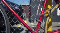 Bicycle Locked up against a fence - alternative transportation in urban areas Stock Footage