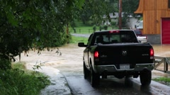 Pickup Truck Drives Through Flood Waters Flowing over Road Stock Footage