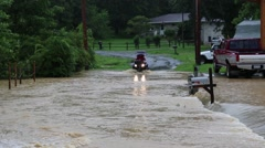 Family Drives ATV (Four Wheeler) Through Flood Waters Flowing Over Road Stock Footage