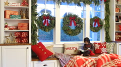 Young girl reading book in house decorated for Christmas Stock Footage