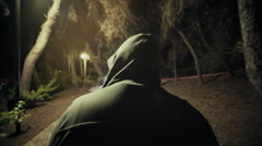 Suspicious hooded figure walks in a dark park at night,,gimbal tracking Stock Footage
