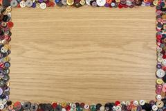 Wooden background with a colorful button border Kuvituskuvat