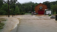 Flood Waters Flow Rapidly over Road near House Stock Footage