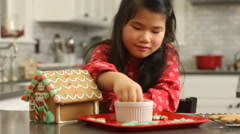 Young girl decorating gingerbread house for Christmas Stock Footage