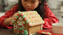 Closeup of young girl decorating gingerbread house for Christmas Stock Footage