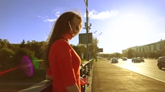 Cheerful pretty brunette girl standing on sunny street. Slow motion video Stock Footage