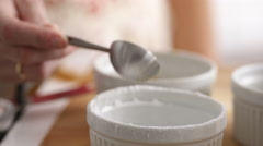 Measuring teaspoon of baking powder into mixing bowl Stock Footage