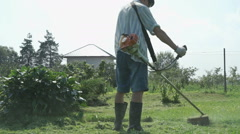 Gardener cuts the grass with lawn string trimmer Stock Footage