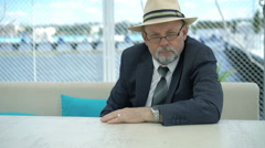 Portrait of old businessman sitting at table outdoor and looking on camera. 4K Stock Footage