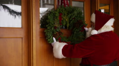 Santa Claus putting wreath on door Stock Footage