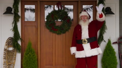 Santa Claus waving by front door Stock Footage