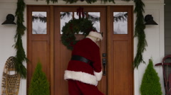 Santa Claus going into front door of home Stock Footage