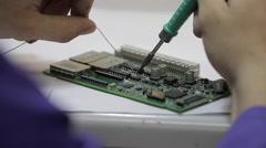 Engineer Solders a motherboard Stock Footage