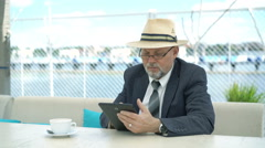 Friendly handsome old man with tablet computer in cafe. 4K Stock Footage