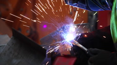 Factory worker solders metal boxes, sparks Stock Footage