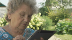 Elderly grandmother holding silver digital tablet Stock Footage