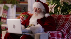 Santa Claus using laptop in living room Stock Footage