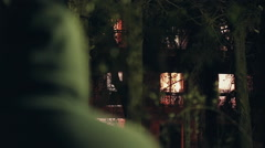 Hooded stalker stalking apartment from a distance at night,rack focus Stock Footage