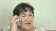 Grandmother having a call on mobile phone indoors Stock Footage