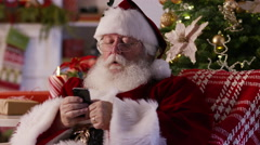 Santa Claus texting with cell phone and taking selfie Stock Footage
